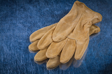 Pair of leather brown protective gloves on scratched metallic ba