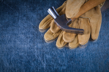 Pair of leather protective gloves with metal claw hammer on scra