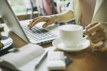 woman holding cup of coffee while working