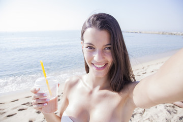 Happy girl drinking a smoothie and taking self portrait photograph with smart phone on beach. Healthy lifestyle