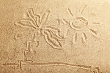 Drawing sun and palm tree on beach sand
