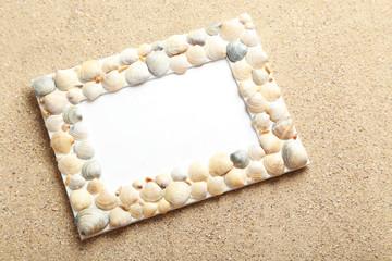 Frame of sea shells on beach sand