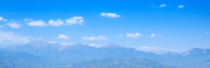 Mountains under bright cloudy sky. Corsica