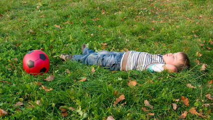 3-year boy is sleeping on a green grass with a ball