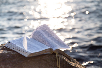 The bible on a stone against the sea