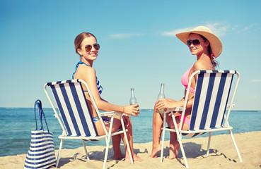 happy women sunbathing in lounges on beach