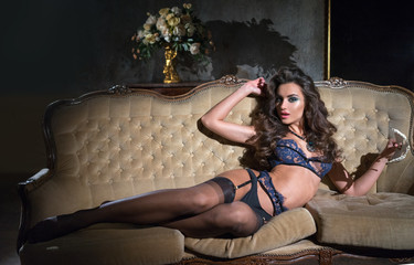 The girl lies on a sofa in a beautiful lingerie.