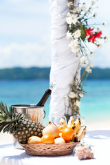 Beautiful wedding arch on tropical beach, focus on bottle