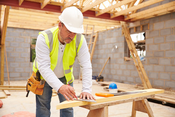 Fototapeta Carpenter Cutting House Roof Supports On Building Site obraz