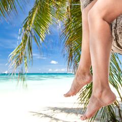 Woman sitting on palm