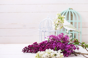 Lilac flowers  and candle on wooden background.