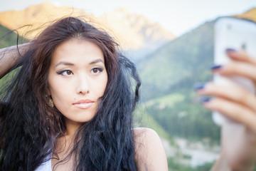 Beautiful asian woman smiling at mountain landscape