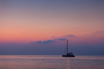 Beautiful catamaran sailing on the background of the sea sunrise
