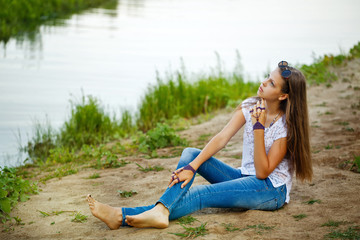 Boho Girl sitting on bank of  river.