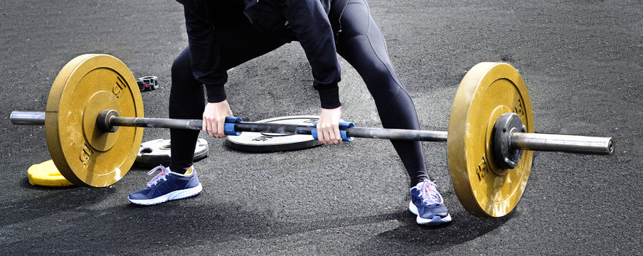 Woman doing deadlift with a barbell.On the neck barbell extenders for additional training of the hands.