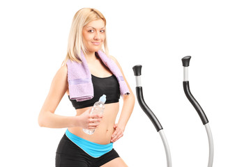 Woman holding a water bottle on a cross trainer machine