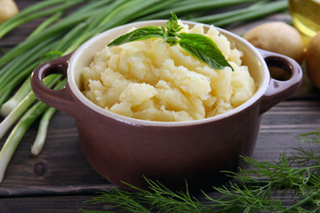 Mashed potatoes in bowl on wooden table, closeup