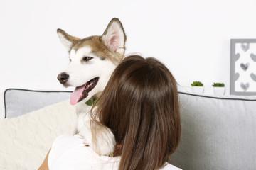 Woman hugging malamute dog in room