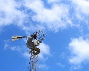 Vintage windmill with cloudy blue sky in background.