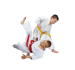An athlete with a yellow belt throws athlete  with a red belt