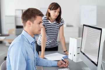 kollegen im büro schauen gemeinsam auf den computer