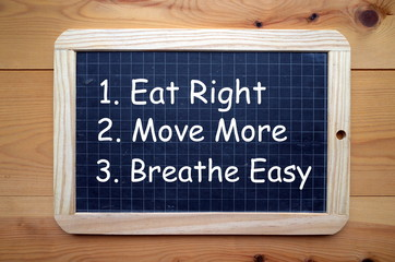 Health and Fitness advice to Eat Right, Move More and Breathe Easy in white text on a slate blackboard