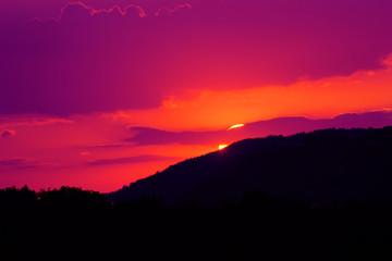 Tramonto viola - il sole che sta tramontando dietro una montagna