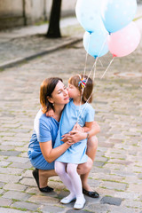Girl kissing mom. Happy woman and her little daughter in the park with balloons. Mother day or birthday concept.