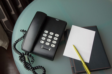 black telephone with paper note