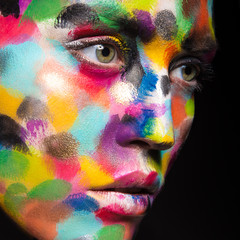 Girl with colored face painted. Art beauty image.