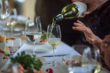 Waiter pouring white wine to senior  in restaurant