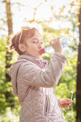 Photo of little girl drinking water with in the park