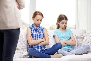 upset guilty little girls sitting on sofa at home