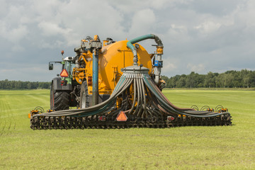 Injecting of liquid manure with tractor and yellow vulture sprea