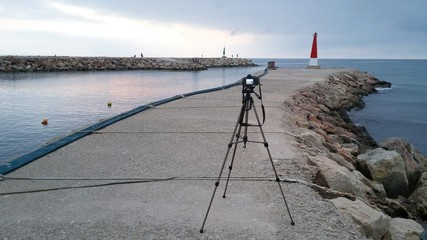 Photographer trypos facing the sunrise on the harbour
