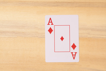 ace of playing card on wooden table