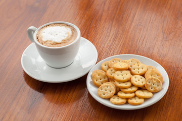 coffee on wood background and biscuits