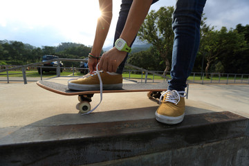 skateboarder hands tying shoelace at skatepark
