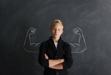 Starker Junge mit Muskeln vor Tafel