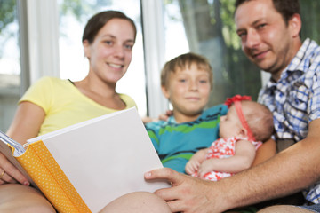 Cute baby and family in front of a book.
