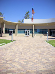 paved building entrance with american and california flag