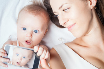 Funny baby girl with mom make selfie on mobile phone