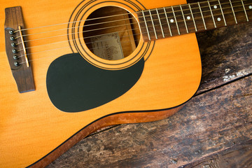 Dreadnought acoustic guitar on a wooden background closeup