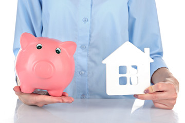 Female hands holding piggy bank and house, closeup