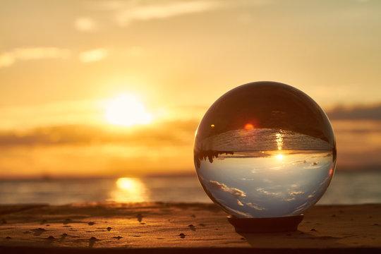 Die Sonne geht über dem Bodensee unter und leuchtet durch eine Glaskugel.