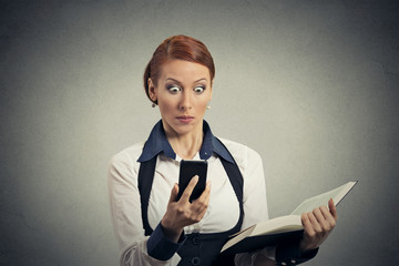 Surprised woman with book looking at phone with disgusting emotion on face