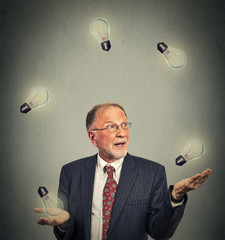 senior business man executive in suit juggling playing with light bulbs