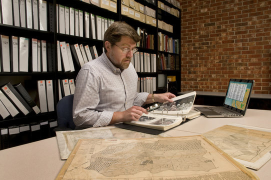 Researcher in Archive Examining Maps and Other Archival Material