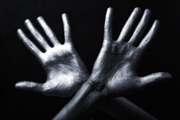 hand in a silver paint isolated on black background