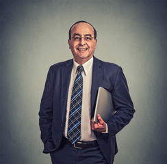 Happy businessman with glasses and laptop standing on gray background